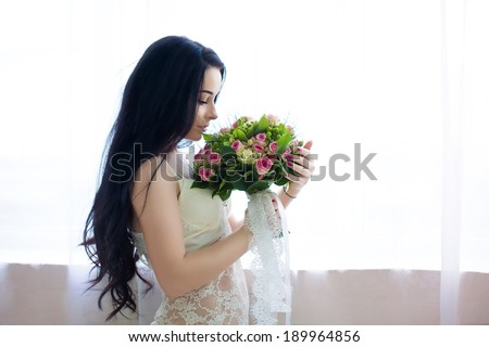 beautiful young bride in a white dress with a wedding bouquet of pink roses. Last preparations for the wedding. Bride waits for her groom. Morning, the bride. #189964856
