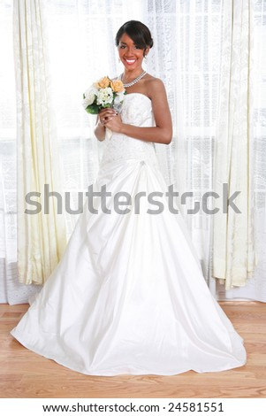 Beautiful Young Bride Looking Out Window In a Rainy Day With Bridal Rose Bouquet