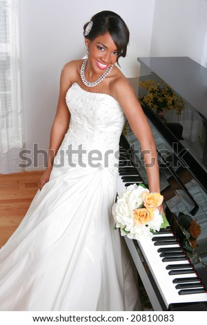 Beautiful Young Bride Standing by Piano With Bridal Rose Bouquet