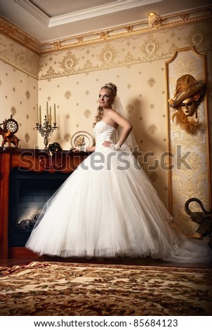 beautiful young bride stands in the antique interior