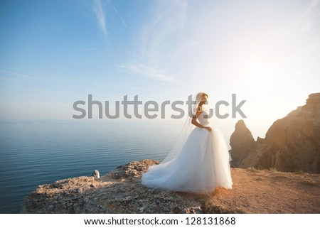 beautiful young bride stands on a rock in the sea rocky landscape