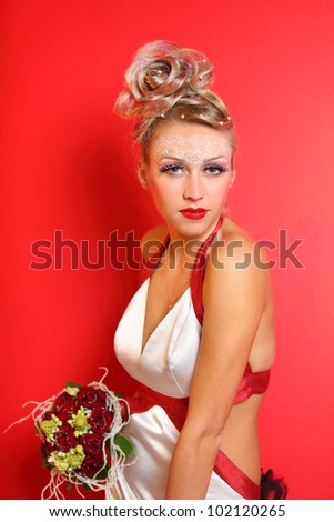 beautiful young bride wearing in original dress with bouquet of roses on red background