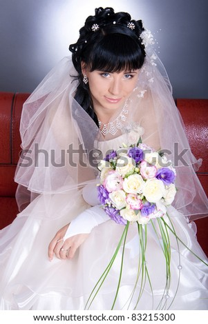 Beautiful young bride with a bright bouquet in hand, sitting on a red couch - stock photo