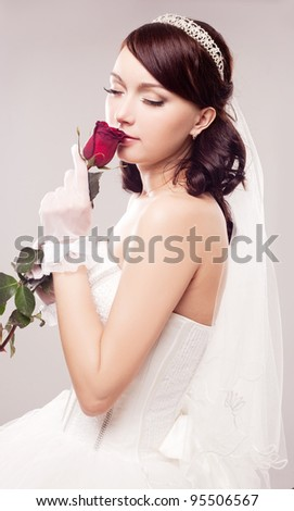 beautiful young bride with a rose, isolated against grey studio background