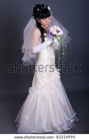 Beautiful young bride with long black hair, with a bunch of flowers. Shooting in the studio