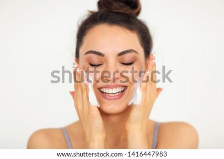Beautiful young brunette caucasian woman washing her face with foam  #1416447983