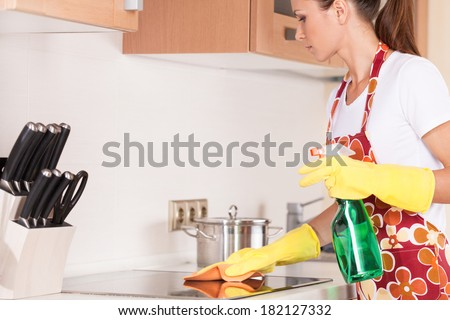 Beautiful young brunette cleaning the kitchen. attractive girl standing in apron and using detergents
