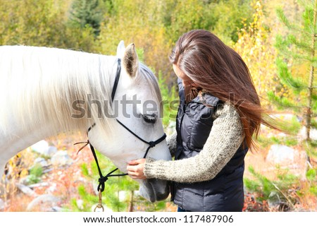 Beautiful young brunette cowgirl with her white horse