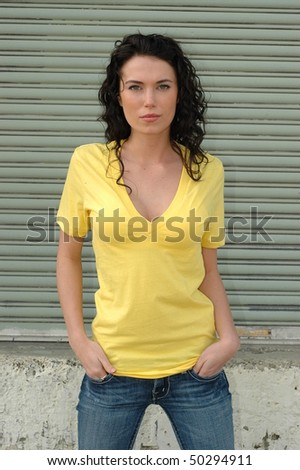 Beautiful, young, brunette female model posing in bright yellow t-shirt and jeans in front of metal garage door.