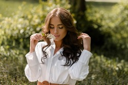 Beautiful young brunette girl sits near a tree on a sunny day in spring, summer, close up