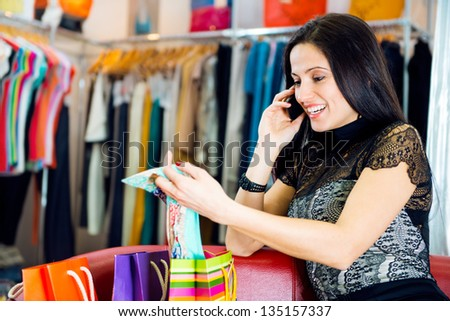 Beautiful young brunette girl talking via phone in clothes boutique