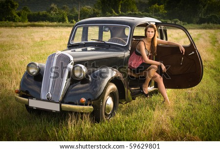 Beautiful young brunette posing with black old timer car.