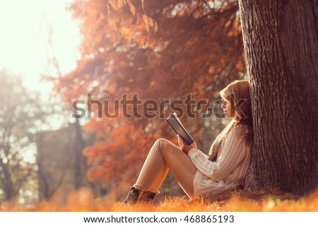 Beautiful young brunette sitting on a fallen autumn leaves in a park, reading a book #468865193
