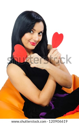 Beautiful young brunette sitting on orange couch with two red Valentine hearts. Isolated on white background.