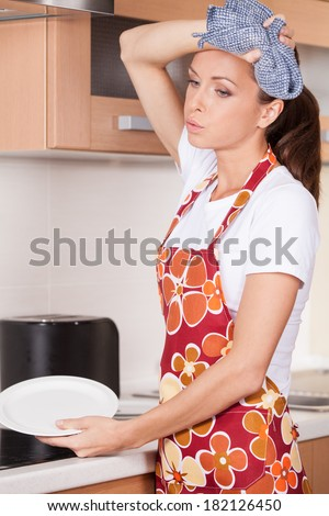 Beautiful young brunette washing dishes. tired and exhausted girl standing in apron