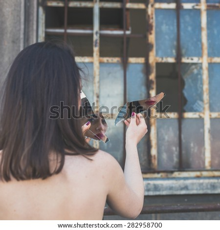 Beautiful young brunette with long hair looking at herself in a broken