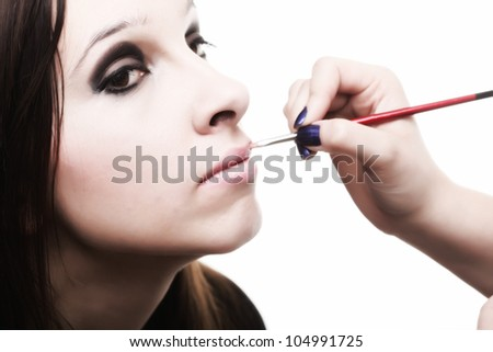 beautiful young brunette woman applying lips make-up zone isolated background