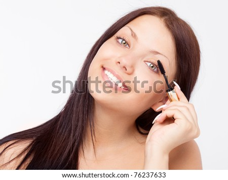 beautiful young brunette woman applying mascara on her eyelashes