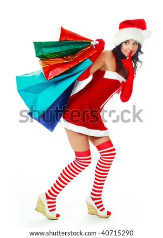 beautiful young brunette woman dressed as Santa with a lot of shopping bags