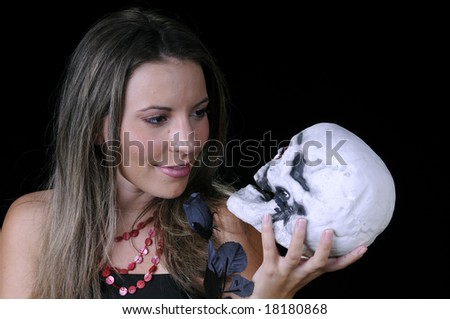 Beautiful young brunette woman holding a black rose and a skull, looking at it, for halloween - stock photo
