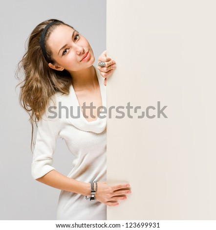 Beautiful young brunette woman holding large white banner for copy space.