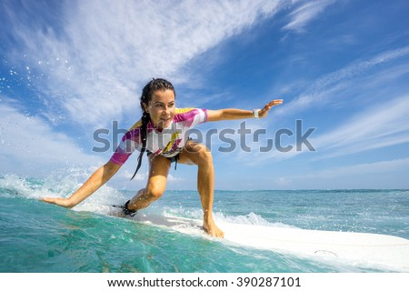 Stock Photo Beautiful young brunette woman in a bright bikini surfing in Mauritius in the Indian Ocean on the background of blue sky, clouds and transparent waves