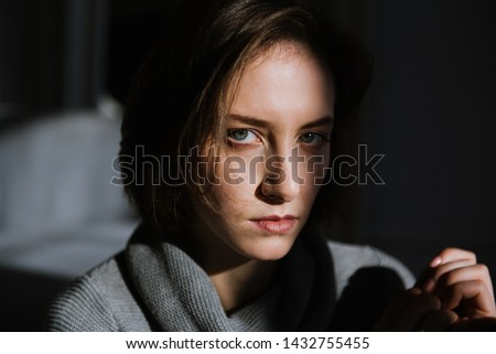 Beautiful young brunette woman in a gray sweater in the studio. Close-up of a young brunette woman. #1432755455
