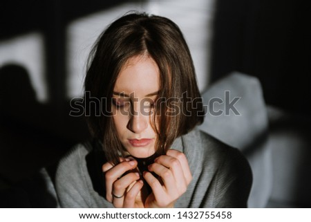 Beautiful young brunette woman in a gray sweater in the studio. Close-up of a young brunette woman. #1432755458