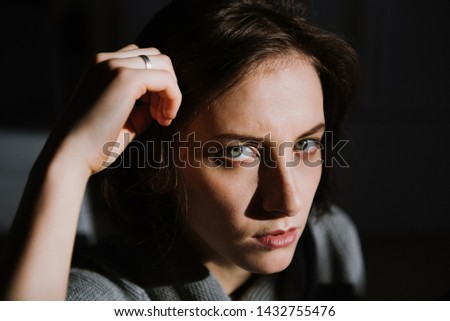Beautiful young brunette woman in a gray sweater in the studio. Close-up of a young brunette woman. #1432755476