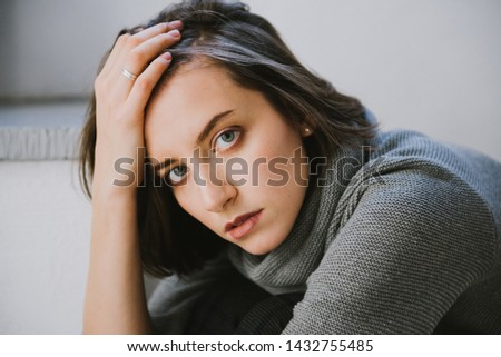 Beautiful young brunette woman in a gray sweater in the studio. Close-up of a young brunette woman. #1432755485