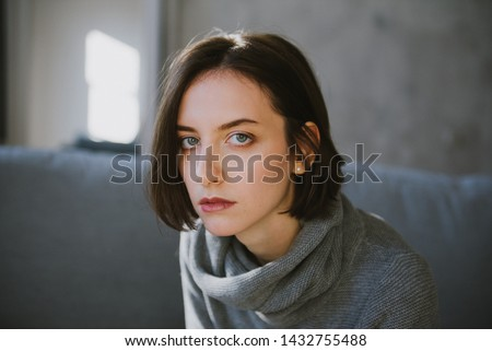 Beautiful young brunette woman in a gray sweater in the studio. Close-up of a young brunette woman. #1432755488