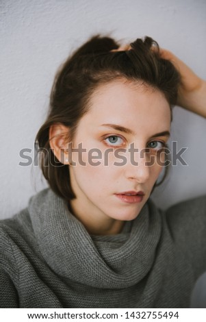 Beautiful young brunette woman in a gray sweater in the studio. Close-up of a young brunette woman. #1432755494