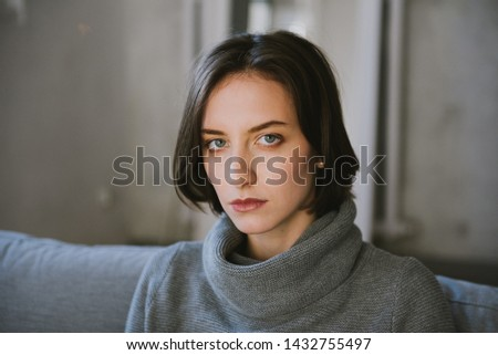 Beautiful young brunette woman in a gray sweater in the studio. Close-up of a young brunette woman. #1432755497