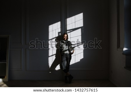 Beautiful young brunette woman in a gray sweater in the studio in the sun. Portraits of a young brunette woman en sun. #1432757615