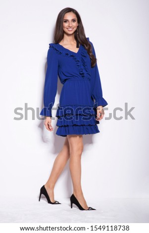 Beautiful young brunette woman in a nice fashionable blue dress. Christmas new year glamour photo.