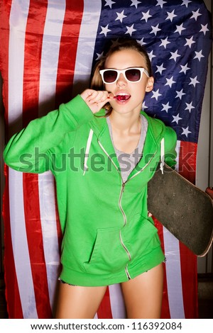 beautiful young brunette woman in style cloth and sunglasses sucking lollipop with national usa flag in background, outdoors
