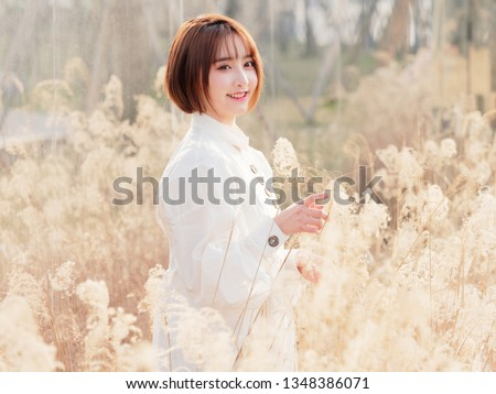 Beautiful young brunette woman in white shirt smiling at camera in sunny day. Outdoor fashion portrait of glamour Chinese cheerful stylish girl, emotions, people, beauty and lifestyle concept.
