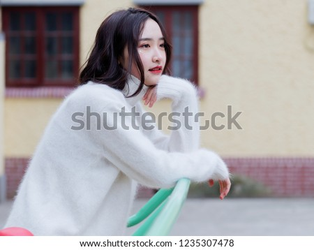 Beautiful young brunette woman looking away with blur house background. Outdoor fashion portrait of glamour young Chinese cheerful stylish lady, emotions, people, beauty and lifestyle concept.