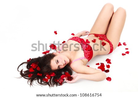 Beautiful young brunette woman lying on white isolated background among red rose petals wearing red sexy bra and pants under wear looking alluring