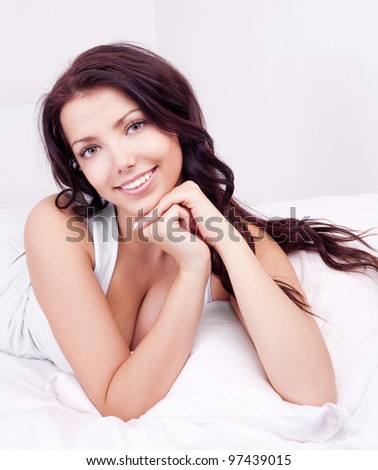 beautiful young brunette woman relaxing in bed at home