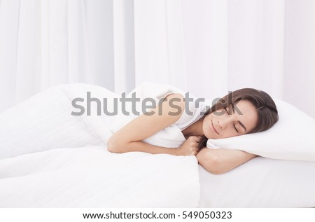 Beautiful young brunette woman sleeping in a white bed.