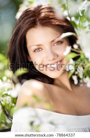 beautiful young brunette woman standing near the apple tree