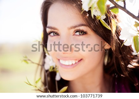beautiful young brunette woman standing near the apple tree on a warm summer day