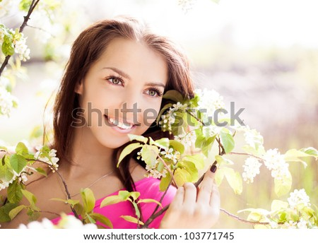 beautiful young brunette woman standing near the  tree on a warm summer day