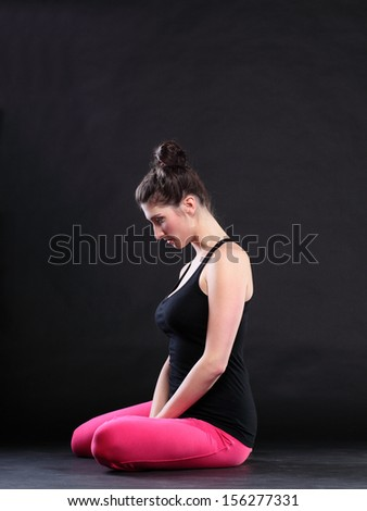 beautiful young brunette woman stretching the muscles of her arms and back, isolated against black background