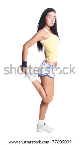 beautiful young brunette woman stretching the muscles of her legs, isolated against white background