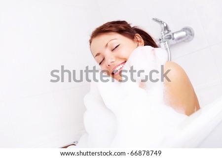 beautiful young brunette woman taking a relaxing bath with foam - stock photo
