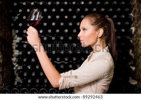 Beautiful young brunette woman tasting wine, checking the color in the wine cellar.