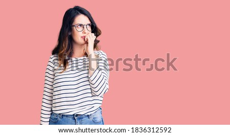 Beautiful young brunette woman wearing casual clothes and glasses looking stressed and nervous with hands on mouth biting nails. anxiety problem.  stock photo