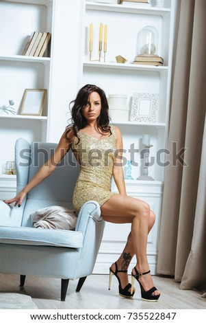 Beautiful young brunette woman wearing short golden dress #735522847